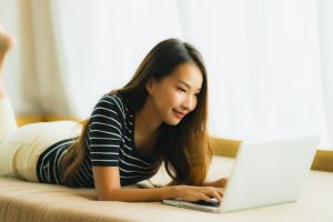 Portrait beautiful young asian woman using computer notebook or laptop on sofa in living room area
