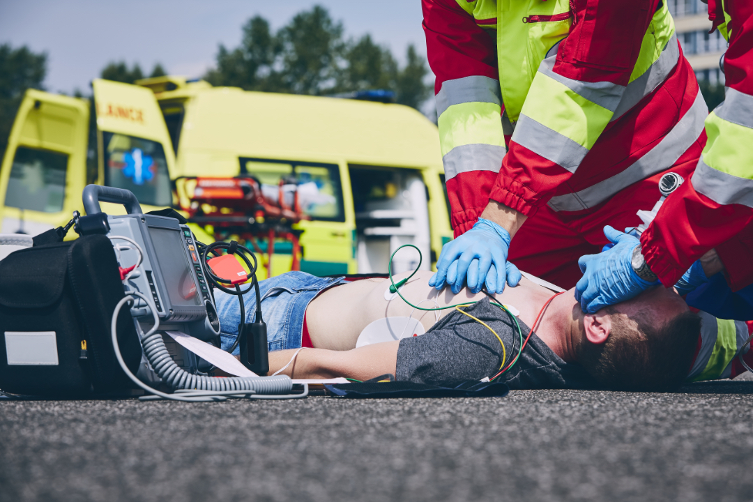 Cardiopulmonary resuscitation. Rescue team (doctor and a paramedic) resuscitating the man on the road.